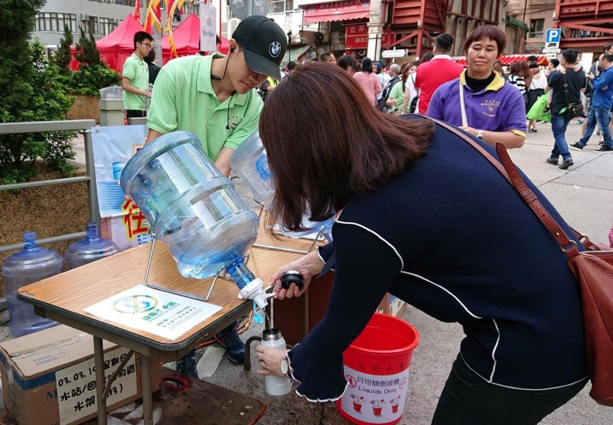 Member of public refilling water at water station